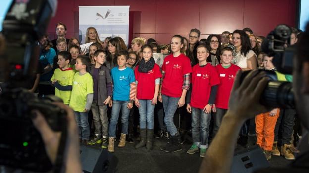 Auf einer Bühne stehen viele Kinder, die einen Preis bekommen.
