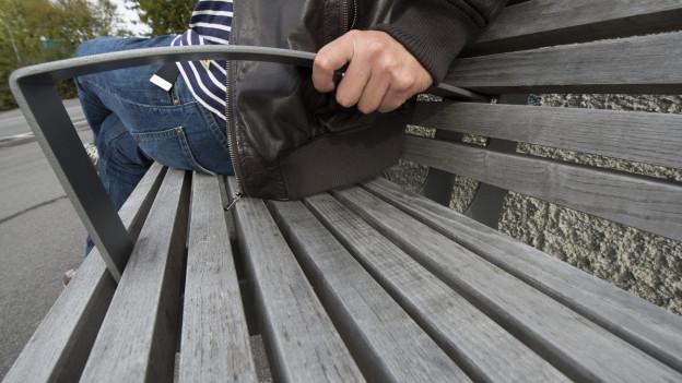 Ein Mann sitzt auf einer Parkbank. Blick von schräg unten.