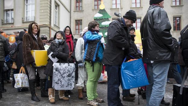 Viele Menschen geben ein Paket mit Lebensmittel ab.
