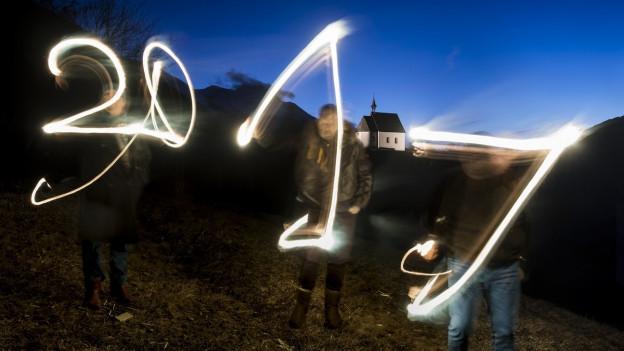 Vier Personen zeichnen mit Licht die Zahl 2017 in die Luft.