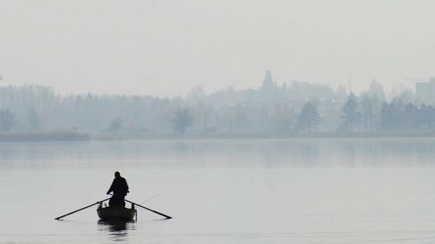 Ein Fischer rudert mit seinem Boot alleine auf einen See hinaus