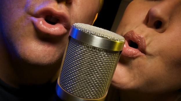 Zwei Menschen singen in Mikrofon