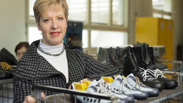 Eine Frau steht bei einem Schuhregal.