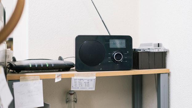 Ein schwarzes Radiogerät steht in einem Regal.