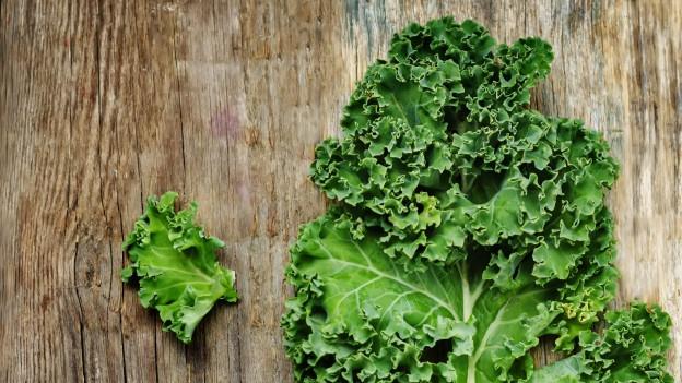Der Kale liegt drapiert auf einer Holzoberfläche. Er ist sehr grün. Das Holz hat einen dunklen Farbton.