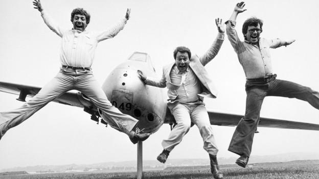 Alex, Guido und Vic Eugster springen gleichzeitig in die Luft. Im Hintergrund steht ein Kleinflugzeug.