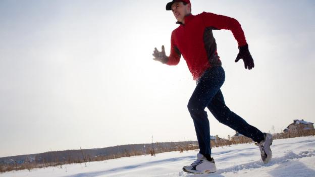 Mann joggt auf Schnee
