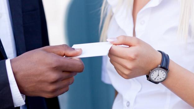 Hände übergeben sich Visitenkarte.