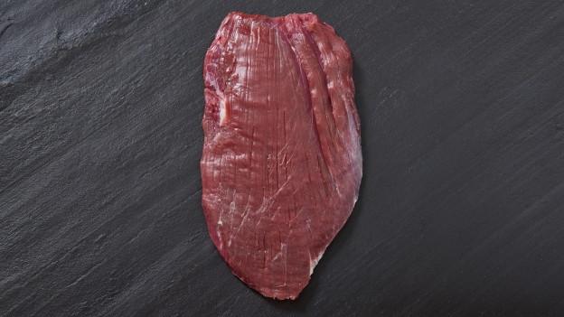 Ein Fleisch liegt auf einer grauen Schiefertafel.