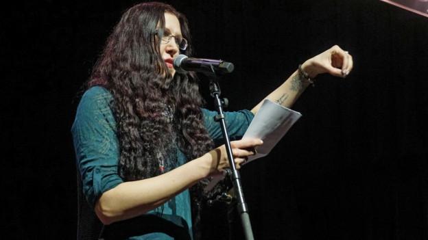 Marianne Lindner steht auf der Bühne der Slam Poetry Szene und hat ihren Auftritt.