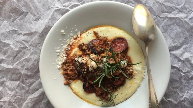 Ein Teller auf Papierhintergrund mit Hackfleisch und Chorizo. Ein Silberlöffel lädt zum Essen ein.