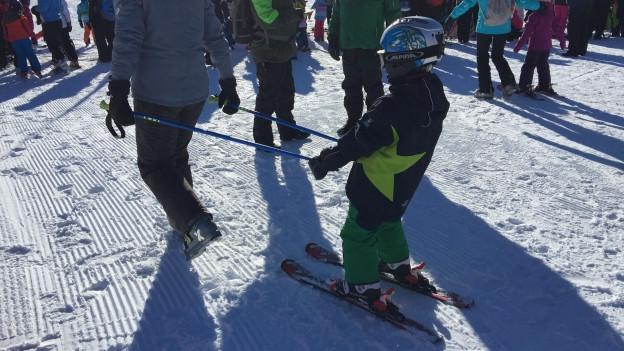 Kind wird von Mutter über die Skipiste gezogen.