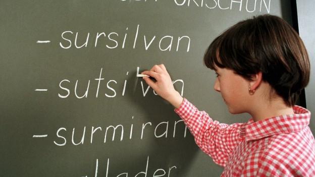 Ein Kind schreibt die Idomsbezeichnungen an die Wandtafel.