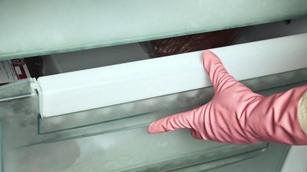 Person mit Handschuh öffnet ein Gefrierfach.
