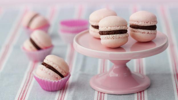 Rosarote Macarons auf einem rosaroten Teller.