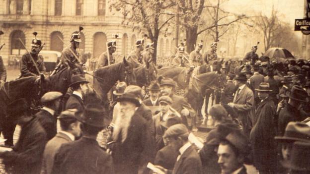 Das Bild zeigt den Paradeplatz 1918. Zu sehen sind Militär-Kavallerie Soldaten, die Streikende einkesseln.
