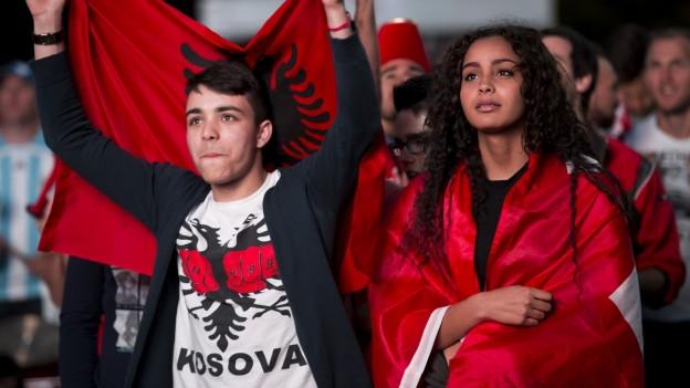 Zwei Fussballfans mit kosovarischer und Schweizer Flagge