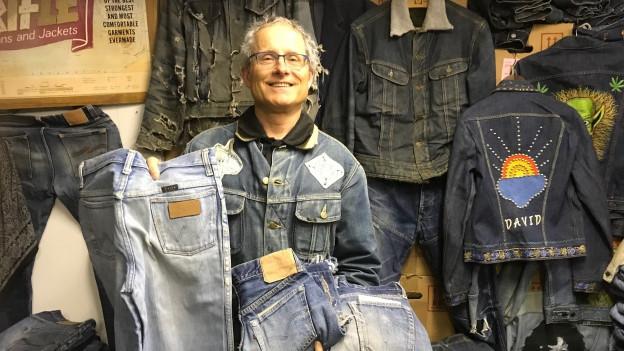 In einem Raum stappeln sich ganz viele Paar Jeans.