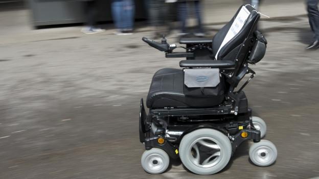 Ein leerer Rollstuhl auf einem grossen Platz.