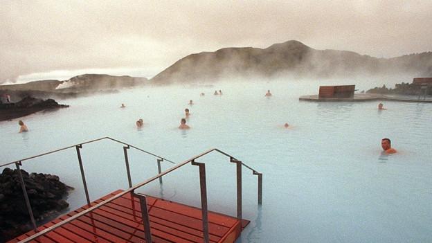 Touristen schwimmen im Pool in schöner Landschaft.