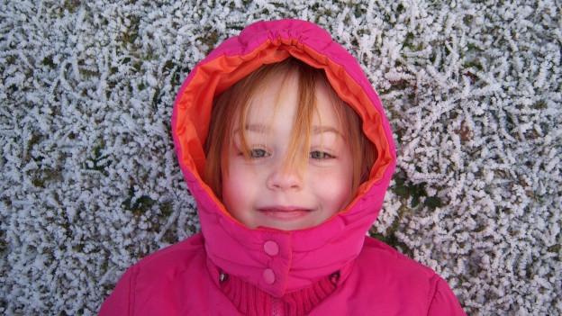 Kind mit Winterjacke liegt im Schnee.