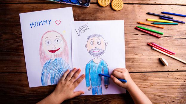 Ein Kind zeichnet Mutter und Vater auf zwei weisse Blätter.