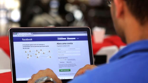Ein Mann sitzt am Computer, auf dem Screen die Facebook-Anmeldemaske.