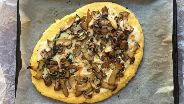 Polenta-Pizza mit Taleggio, Pilzen und frischem Estragon auf einem Blech.