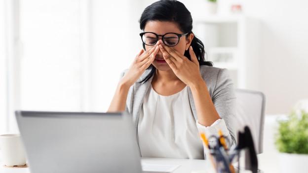 Frau vor dem Computer reibt sich die Augen.