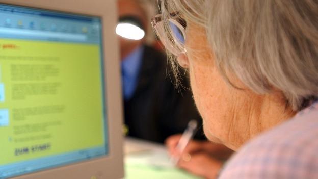 Alte Frau sitzt an einem Computer
