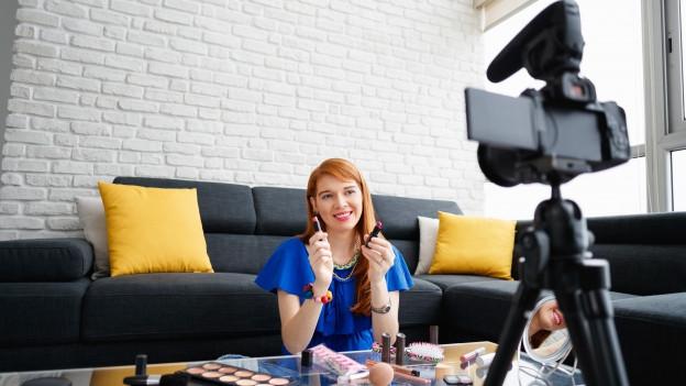 Mädchen sitzt vor Kamera und zeigt Schminksachen