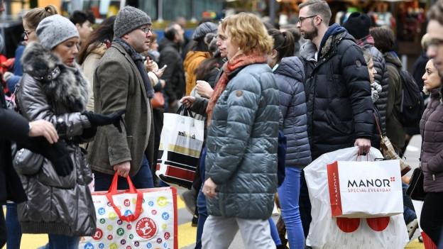 Menschen im Einkaufsstress, mit Taschen unterwegs.