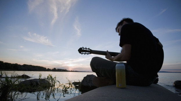 Ein Mann sitzt in der Abenddämmerung am See und spielt Gitarre.