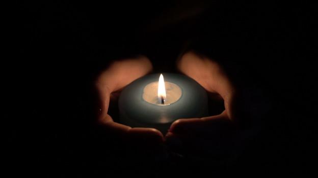 Zwei Hände umfassen im Dunkeln eine grünlich-blaue Kerze.