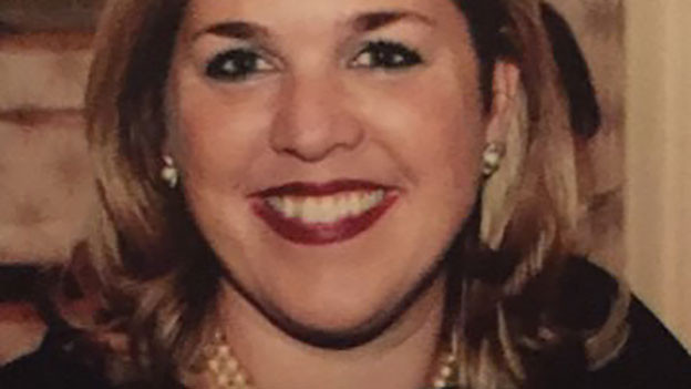 Karen Weick trägt schulterlanges Haar, sitzend in einem schwarzen Abendkleid.