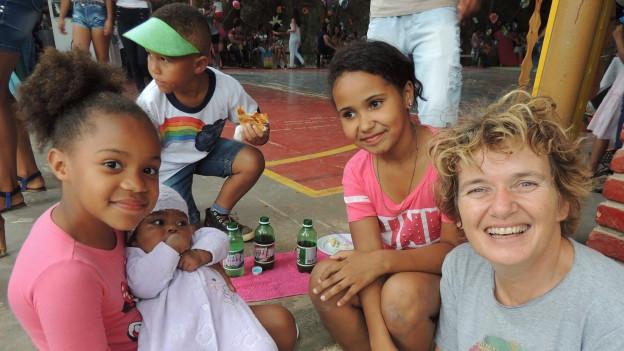 Pause in der Schule: Heidi Caluori sitzt mit Schülerinnen auf der Treppe.