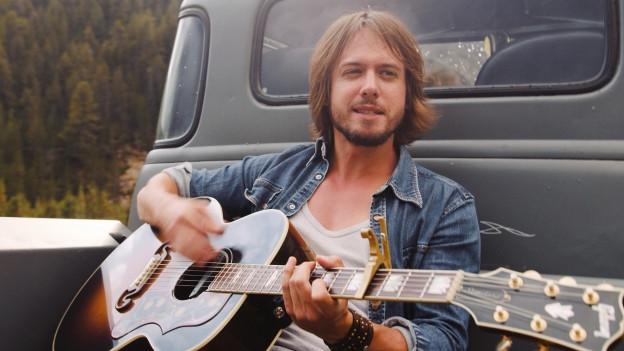 Tobey Lucas mit Gitarre auf einem Pickup.