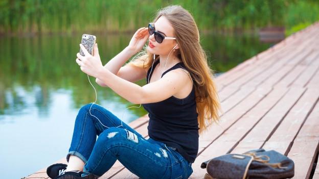 Frau mit Handy am Wasser.