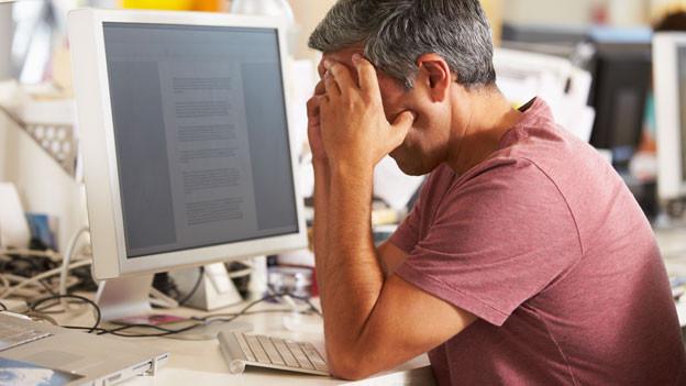 Ein Mann sitzt am Computer und hält sich die Hände vor den Kopf..