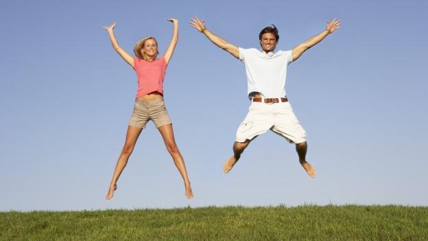 Mann und Frau springen auf Wiese in die Luft