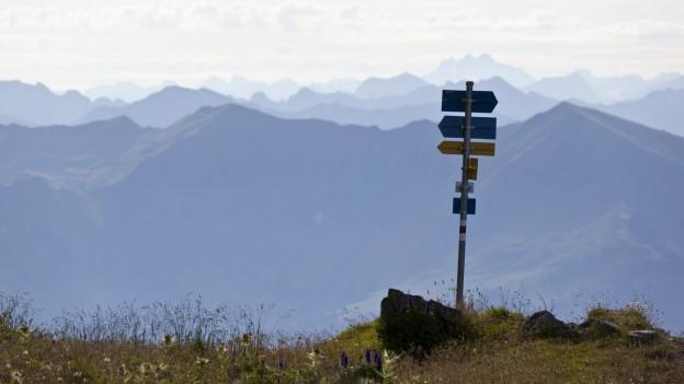 Ein Wegweiser zeigt in den Alpen mehrere Richtungen an.
