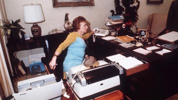 Eine Sekretärin in einem Büro in ihrem Element. Filmstill aus Film von 1976 über Watergate Affäre.