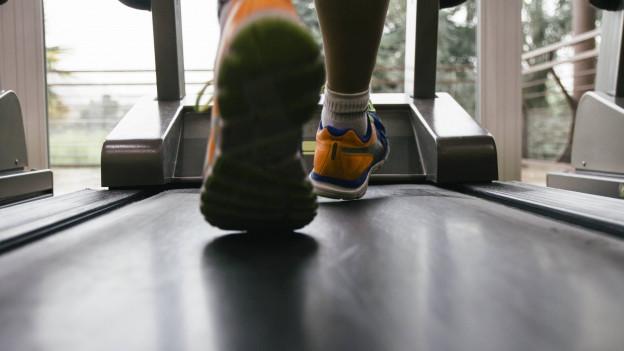 Sportlerfüsse auf Laufband.