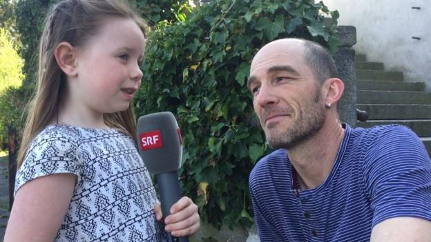 Die siebenjährige Marlena hält ein SRF Mikrofon und interviewt den Mundartsänger Andrew Bond.