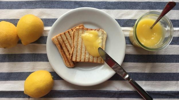 Zitronen, ein Glas Lemon Curd und ein Teller mit Toastbrot.
