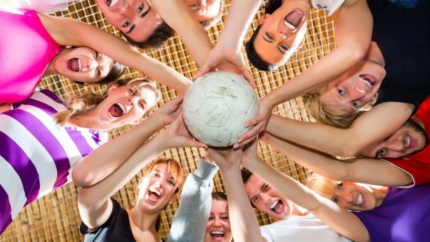 Eine Gruppe Menschen hält einen Ball in der Mitte