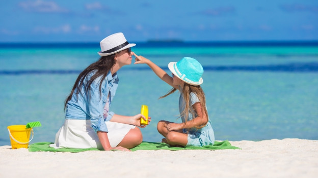 Sonnencreme einreiben, Kind hilft Mutter beim Gesicht.