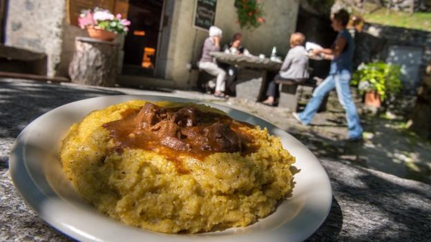 Teller mit Polenta im Vordergrund, dahinter ist unscharf ein Tessiner Grotto zu erkennen. Draussen sitzen an einem Steintisch mehrere Personen, eine Kellnerin geht vorbei.