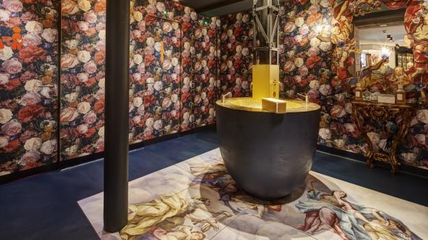 Goldener, runder Waschtisch vor blumigen Toiletten-Türen