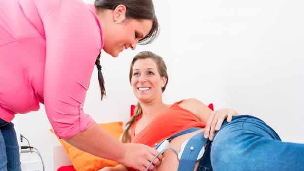 Eine Frau untersucht mit Stetoskop eine Schwangere.